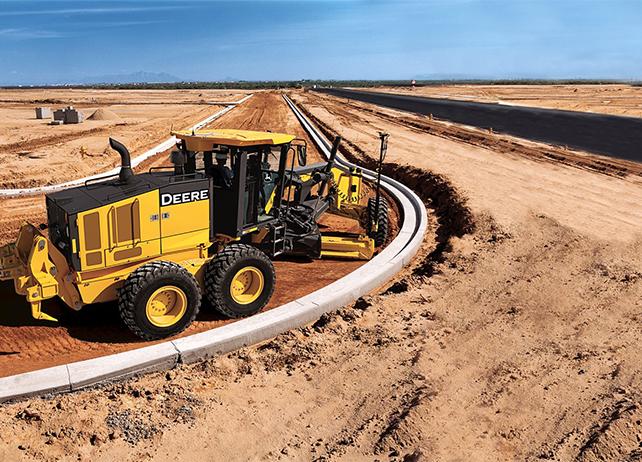 John Deere motor grader levels ground for a road in the desert